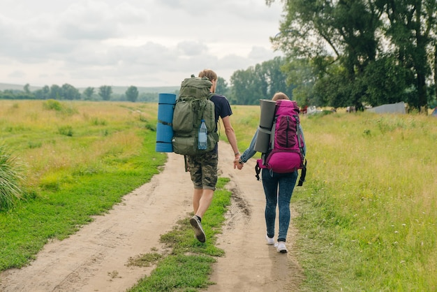 Fashionable love couple with backpacks walk. tourist girl and man backpackers