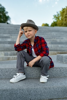 Fashionable macho boy in hat and sunglasses waiting for a girl. kid having fun outdoors, happy childhood