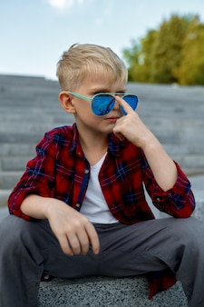 Fashionable macho boy waiting for a girl on stairs. kid having fun outdoors, happy childhood