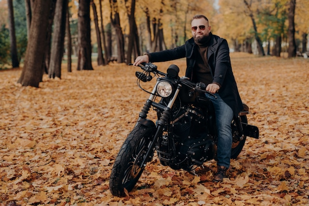 Fashionable male motorcycle driver poses on black motorbike, wears protective sunglasses