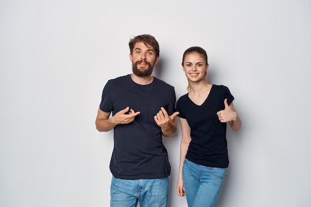Модный мужчина и женщина в черных солнцезащитных очках футболки, позирующих студийный образ жизни