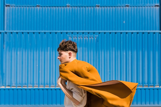 Fashionable man in front of blue wall