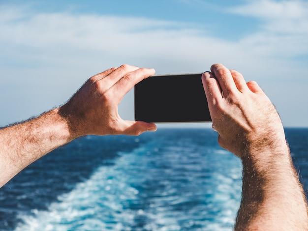 Fashionable man holding a mobile phone on the deck