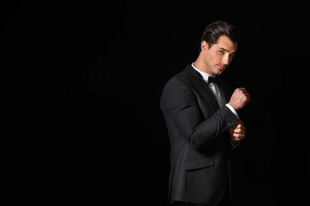 Модный мужчина в формальной одежде на темной стене с копией пространства