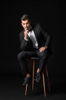 暗い表面に対して椅子に座っているフォーマルな服を着たファッショナブルな男