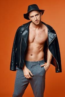 Модный мужчина в кожаной черной куртке обнаженного торса позирует в студии самоуверенности