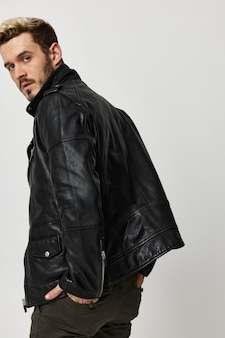 革のジャケットを着たファッショナブルな男が頭を後ろに向けた