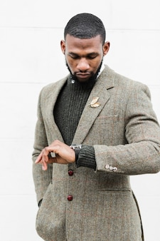 Fashionable man looking at his watch