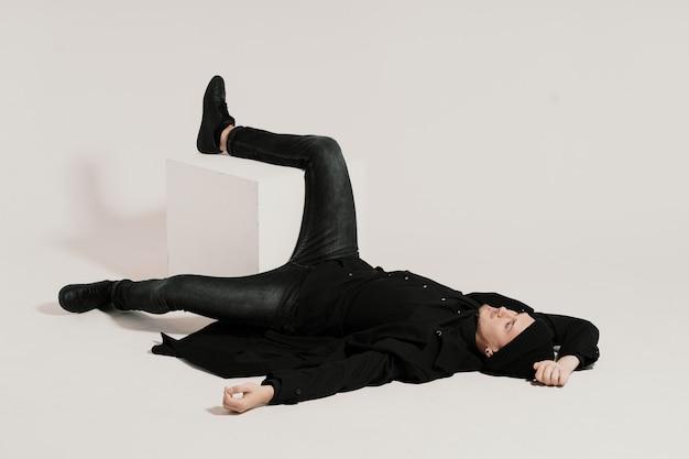 Uomo alla moda che si trova sul bianco con una gamba su un cubo