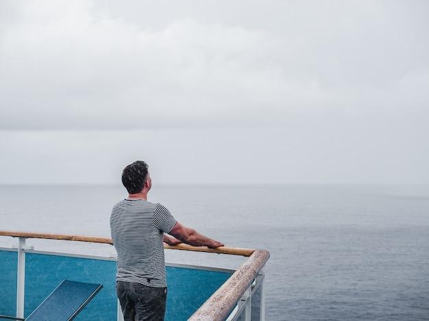 바다 파도의 배경에 대해 크루즈 라이너의 빈 갑판에 유행 남자.
