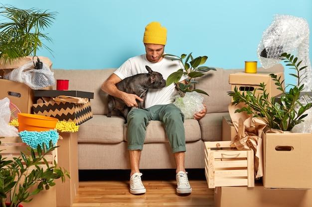 ファッショナブルな男性がお気に入りのペットと居心地の良いソファでポーズをとる