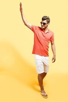 Fashionable man saluting walking against yellow