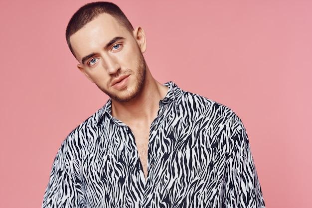 自信のピンクの背景をポーズするファッショナブルな男のシャツ