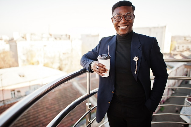 Fashionable man in suit and glasses with cup of coffee at hands posed on balkony at office