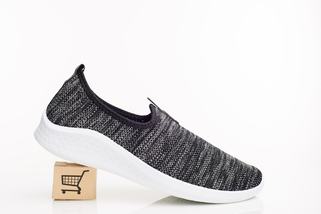 Fashionable man walking shoes with box on a white background. the concept of purchase with delivery