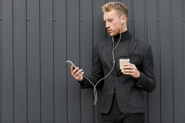 Fashionable man with coffee looking at smartphone