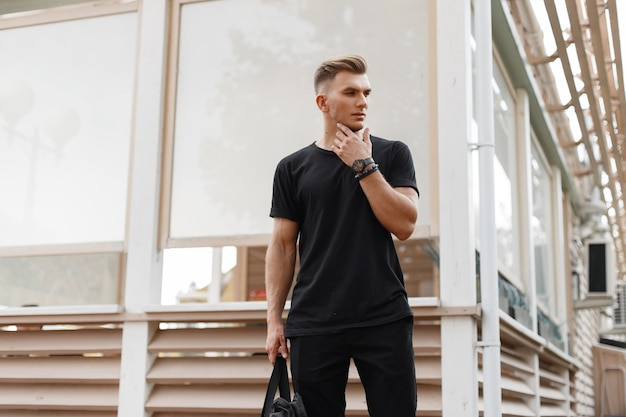Fashionable man with hairstyle in black mockup shirt on the street near a wooden building