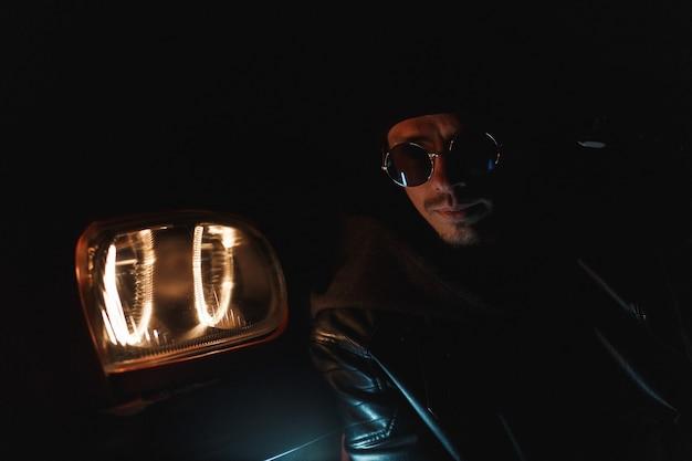 검은 가죽 재킷에 세련된 선글라스를 낀 세련된 남자는 밤에 헤드라이트 근처에 앉는다