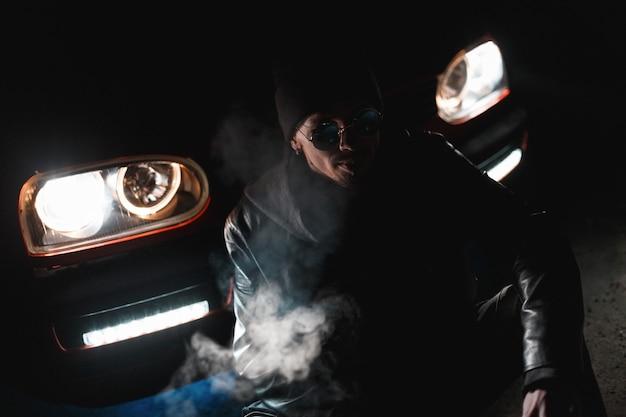검은 가죽 재킷에 선글라스와 모자를 쓴 세련된 남자는 밤에 헤드라이트가 있는 차 근처에 앉아 있습니다. 어둠 속에서 남성 실루엣