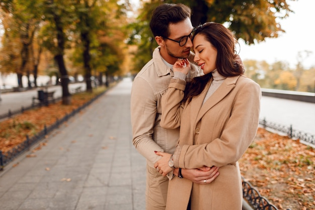 Fashionable man and woman embarrassing while dating in autumn park. wearing stylish beige coats. romantic mood.