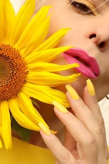 긴 손톱에 유행 매니큐어는 해바라기를 가진 여자에 노란색 매니큐어로 덮여 있습니다.