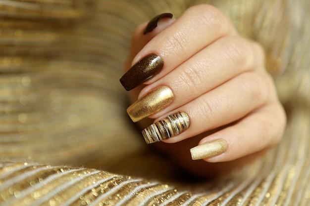 매니큐어의 무광택 황금색과 긴 손톱 모양에 갈색의 세련된 매니큐어.