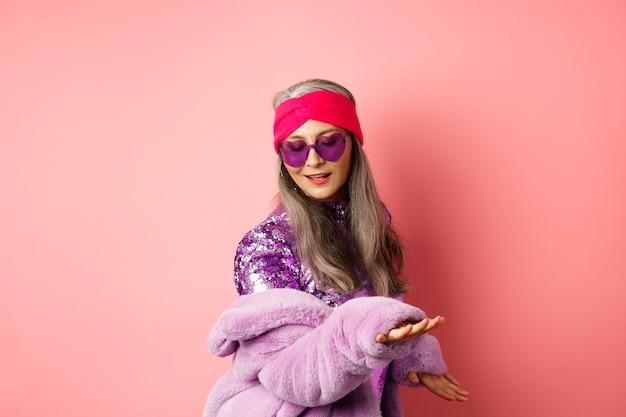 ピンクの背景の上に立って、パーティーで踊り、楽しんでリラックスして、きらびやかなドレスを着たファッショナブルな成熟したアジアの女性。