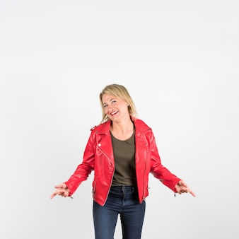 Fashionable mature woman in red leather jacket standing against white background