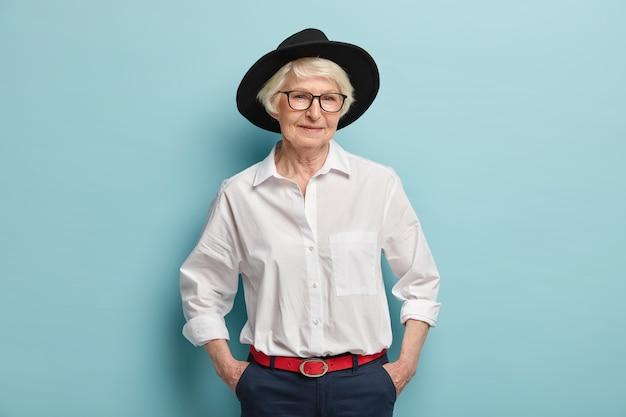 유행 성숙한 여인은 세련된 검은 모자, 흰색 셔츠와 빨간 벨트가 달린 바지를 입고 주머니에 손을 넣고 파란색 벽 위에 고립 된 기쁜 표정을 가지고 있습니다. 사람, 나이 및 패션 컨셉