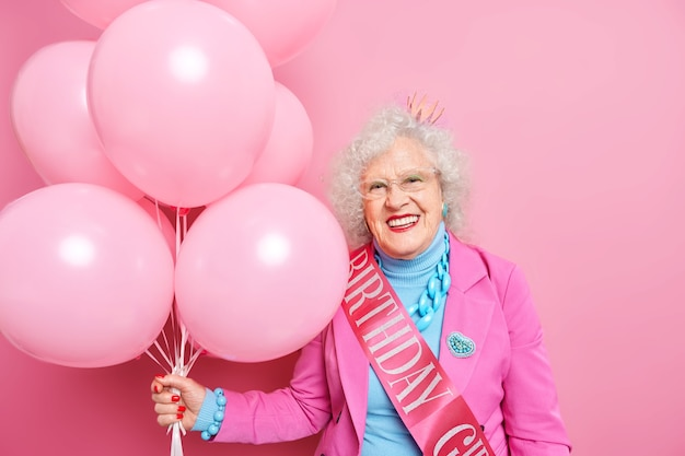 Fashionable mature wrinkled lady wears stylish outfit with jewelry holds bunch of helium balloons celebrates her 100th birthday