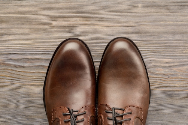 Fashionable men's classic brown shoes on a wooden