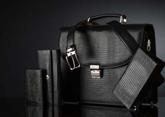 暗い背景にファッショナブルなメンズレザーアクセサリーのセット。ブリーフケース、財布、ベルト