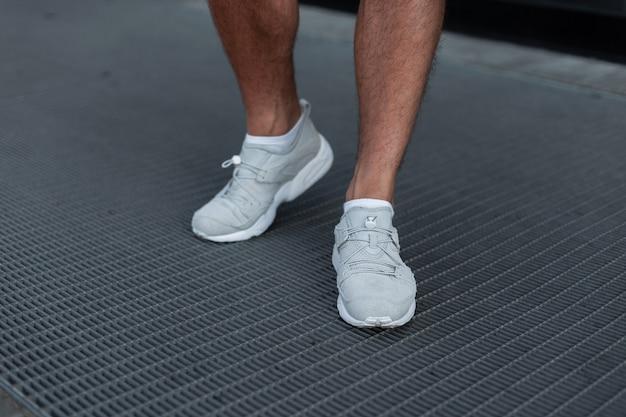 ファッショナブルなメンズホワイトスポーツスニーカー。スタイリッシュなメンズシューズ。カジュアルなデザイン。男性の足のクローズアップ。夏のスタイル。