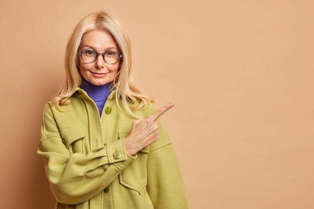 Модная женщина средних лет носит очки и зеленое осеннее пальто, указывая на пространство для копирования