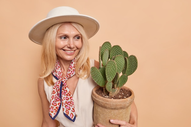 Fashionable middle aged woman with fair hair healthy skin carries pot of succulent green cactus likes home plants wears stylish outfit hat on head smiles pleasantly isolated over brown wall