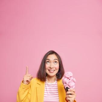 La ragazza millenaria alla moda con i capelli corti scuri punta in alto sullo spazio vuoto della copia dimostra qualcosa sul muro rosa mangia un delizioso gelato al lampone contenente molte calorie