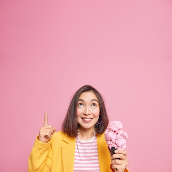 빈 복사본 공간에 짧은 검은 머리 포인트 오버 헤드를 가진 유행 밀레 니얼 소녀는 분홍색 벽 위에 무언가를 보여줍니다 많은 칼로리를 포함하는 맛있는 라즈베리 아이스크림을 먹고