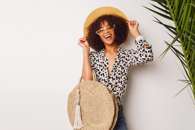 Fashionable mix race girl in trendy blouse and straw hat  standing over white wall. perfect white  smile. shopping mood.