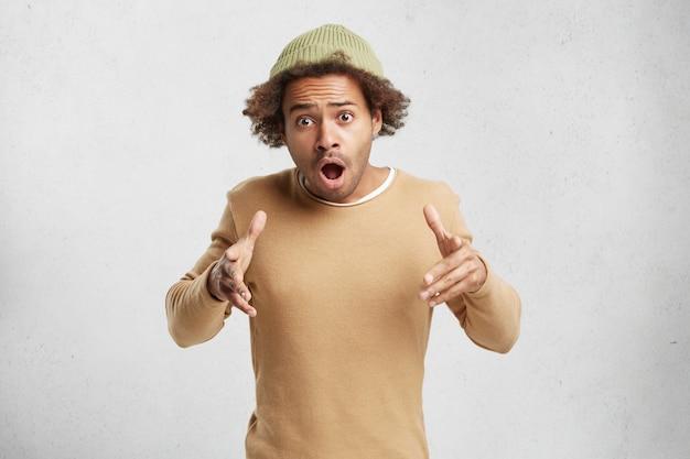 トレンディな帽子とセーターでファッショナブルな混血のティーンエイジャー、困惑のジェスチャー