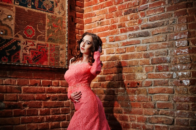 Fashionable model girl at pink evening dress with brick wall.