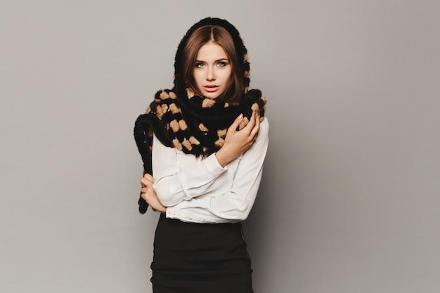 黒いスカート、白いブラウス、灰色の背景のスタジオでポーズをとる流行の毛皮のスカーフで完璧なメイクをしたファッショナブルなモデルの女の子、孤立しています。
