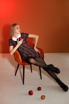 スタジオの秋の背景にオレンジ色の椅子にスタイリッシュな秋のイメージのファッショナブルなモデル