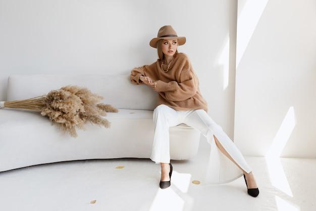 明るいスタジオで秋の服を着たファッショナブルなモデル。秋のファッションブログ