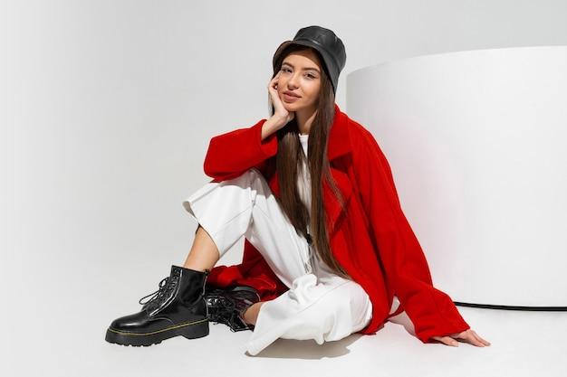 Модная модель в стильной шляпе, красном пальто и сапогах позирует на белой стене