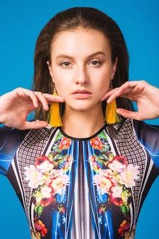Modello alla moda che posa nello studio in outfit alla moda