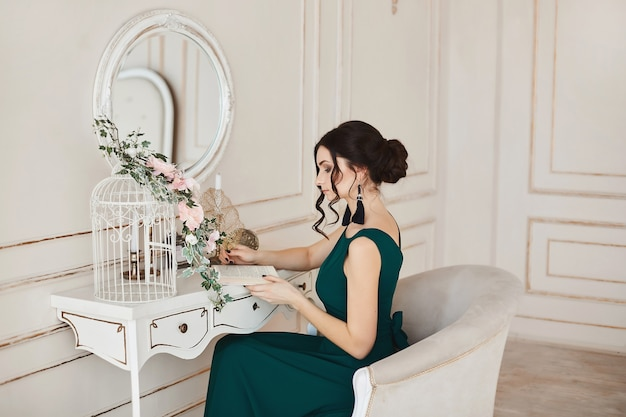 Fashionable model with stylish hairstyle in evening dress sits at the dressing table