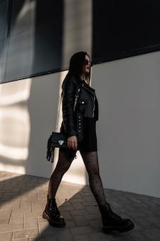 세련된 검은 옷에 멋진 선글라스를 낀 세련된 모델 여성, 가죽 재킷과 부츠, 세련된 핸드백이 있는 도시 산책