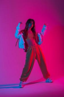 다양한 색상의 자외선으로 스튜디오에서 포즈를 취한 신발을 신고 세련된 운동복을 입은 세련된 모델 젊은 여성. 밝은 분홍색 네온 불빛이 있는 방에서 춤추는 아름다운 소녀 댄서. 스타일.
