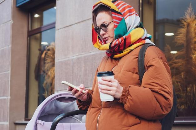 Модная современная мама с коляской на прогулке по городу, осень. мама водит коляску по улице, крупный план.