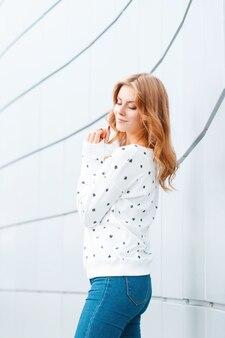 春の暖かい日に街のモダンな壁の近くに青いトレンディなジーンズの白いセーターでスタイリッシュな髪型を持つファッショナブルな現代の若い女性